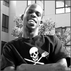 Image of Leroy Moore, smiling, with his arms crossed over his chest. He is wearing a black t-shirt with a skull and crossbones.
